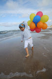 Little girl playing with balloons on the beach Stock Photos