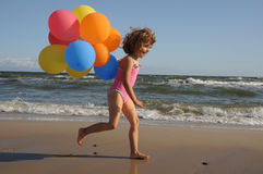 Little girl playing with balloons on the beach.  Royalty Free Stock Photo