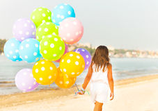Little girl playing with balloons at the beach. Happy little girl playing with balloons at the beach Royalty Free Stock Images