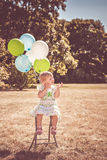 Little girl playing with balloons and bubbles Royalty Free Stock Photos