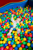 Little girl playing in the balls Royalty Free Stock Photo