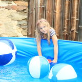 Little girl playing with balls in pool Stock Images