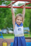 Little girl playing on bar of playground Royalty Free Stock Photo