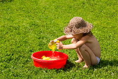 Little girl playing in a basin of water on grass Stock Photo