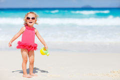 Little girl playing at beach. Adorable toddler girl playing with beach toys on white sand beach Royalty Free Stock Image