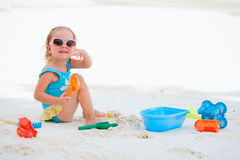 Little girl playing at beach. Adorable toddler girl playing with beach toys on white sand beach Royalty Free Stock Photo
