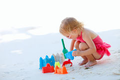 Little girl playing at beach. Adorable toddler girl playing with beach toys on white sand beach Royalty Free Stock Images