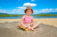 Little girl playing on beach. Under a big umbrella Royalty Free Stock Photos