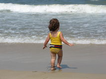 Little girl playing on beach Stock Photos