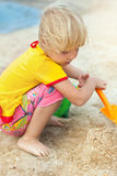 Little girl playing on a beach Stock Photography