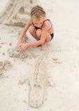 Little girl playing on the beach. Stock Images
