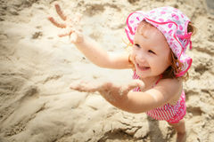 Little girl playing on the beach Royalty Free Stock Photos