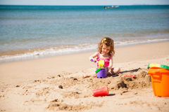 Little girl playing at the beach. Cute little girl in a bathing suit playing with sand at the beach Royalty Free Stock Image