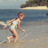Little girl playing on the beach. At the day time Stock Photography