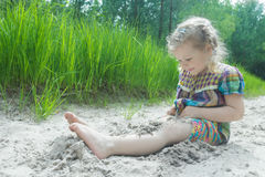 Little girl playing on beach dune and burying herself in white sand at summer pinewood background Royalty Free Stock Image