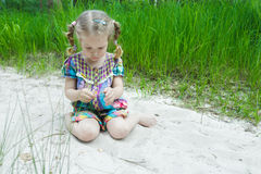 Little girl playing on beach dune and examining little yellow leaf in her hand stock image