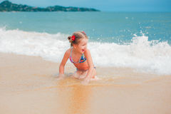 Little girl playing on beach. stock photo