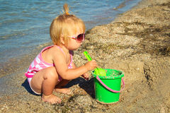 Little girl playing on the beach with pail and shovel. Royalty Free Stock Images