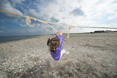 Little girl playing on a beach Stock Image
