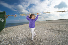 Little girl playing on a beach Royalty Free Stock Image