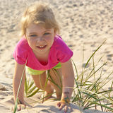Little girl playing in the beach sand Royalty Free Stock Photos