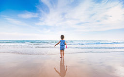Little girl playing on the beach in sunset Royalty Free Stock Photo