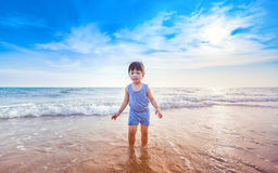 Little girl playing on the beach in sunset Royalty Free Stock Photos