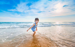 Little girl playing on the beach in sunset Stock Photo