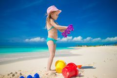 Little girl playing with beach toys during. Adorable girl playing on the beach with white sand Royalty Free Stock Images