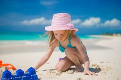 Little girl playing with beach toys during. Adorable girl playing on the beach with white sand Stock Photography