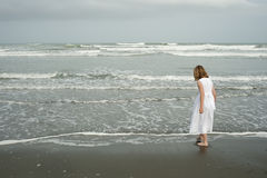 Little girl playing on beach in white dress Royalty Free Stock Photo