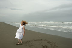 Little girl playing on beach in white dress Stock Image