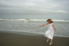 Little girl playing on beach in white dress Stock Photography