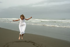 Little girl playing on beach in white dress Royalty Free Stock Photos