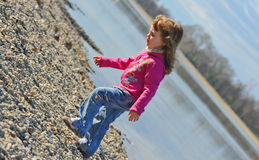 Little girl playing at the beach in winter Royalty Free Stock Images