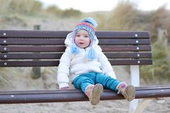 Little girl playing on the beach at winter. Portrait of cute toddler girl in white warm jacket and colorful knitted hat sitting on the bench in the dunes on the Stock Images