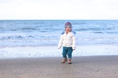 Little girl playing on the beach at winter Royalty Free Stock Photography