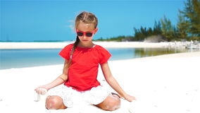 Little girl playing with beautiful white sand at tropical beach. Slow motion. SLOW MOTION: Girl playing with beautiful white sand at exotic beach stock footage