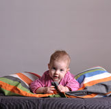 Little girl playing on the bed. Six month old baby playing with pillows and laying on the bed with candid expression. Studio shot against grey background stock photos