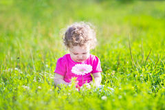 Little girl playing with a big pink flower in the garden Royalty Free Stock Images