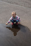 Little girl playing in a big puddle Royalty Free Stock Photography