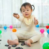 Little girl playing with black domino Stock Images