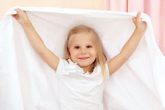 Little girl playing with blanket royalty free stock photography