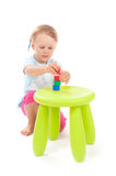 Little girl playing with blocks on the stool Royalty Free Stock Image