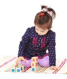 Little girl playing with blocks on which were Royalty Free Stock Photos