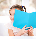 Little girl is playing with book Stock Photo