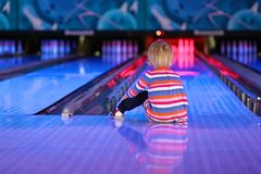 Little girl playing bowling Stock Images
