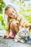 Little girl with a cat outdoors. Little girl playing with a british cat outdoors Royalty Free Stock Photo