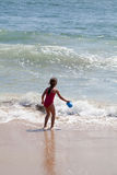 Little Girl Playing with a Bucket on the Beach Stock Image