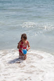 Little Girl Playing with a Bucket on the Beach Stock Photo